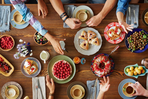 A table full of cakes and pies for the holidays is full of food indulgences that are packed with carbs.