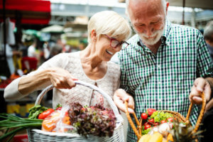 An older woman and man at the local market. They're calorie counting so their basket is full of fresh fruits and vegetables.
